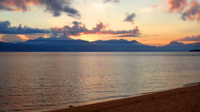 The sun coming out from Biliran mainland's mountains, as seen from Higatangan Island sand bar - Philippines