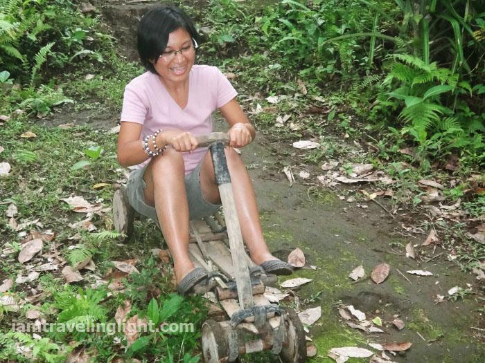 woman happy in ligiron, contraption like wooden bike, four wheels, Valencia, Negros Oriental