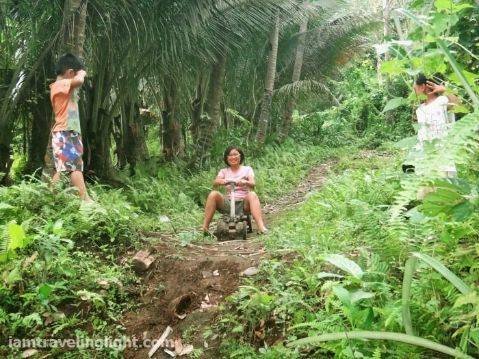 woman in ligiron riding downhill, contraption like wooden bike, four wheels, Valencia, Negros Oriental