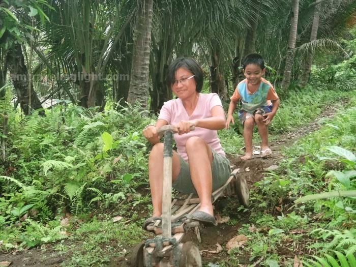 woman in ligiron riding downhill with kid cheering on, contraption like wooden bike, four wheels, Valencia, Negros Oriental