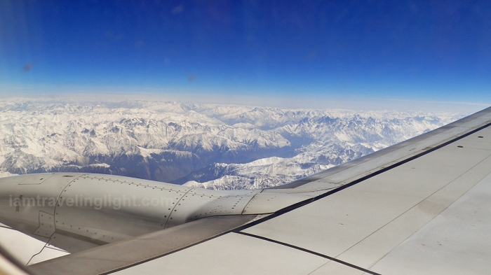 Himalayas mountain range medium shot, tail end winter, view from the plane, with aircraft wings, flight to Leh from New Delhi, India.jpg